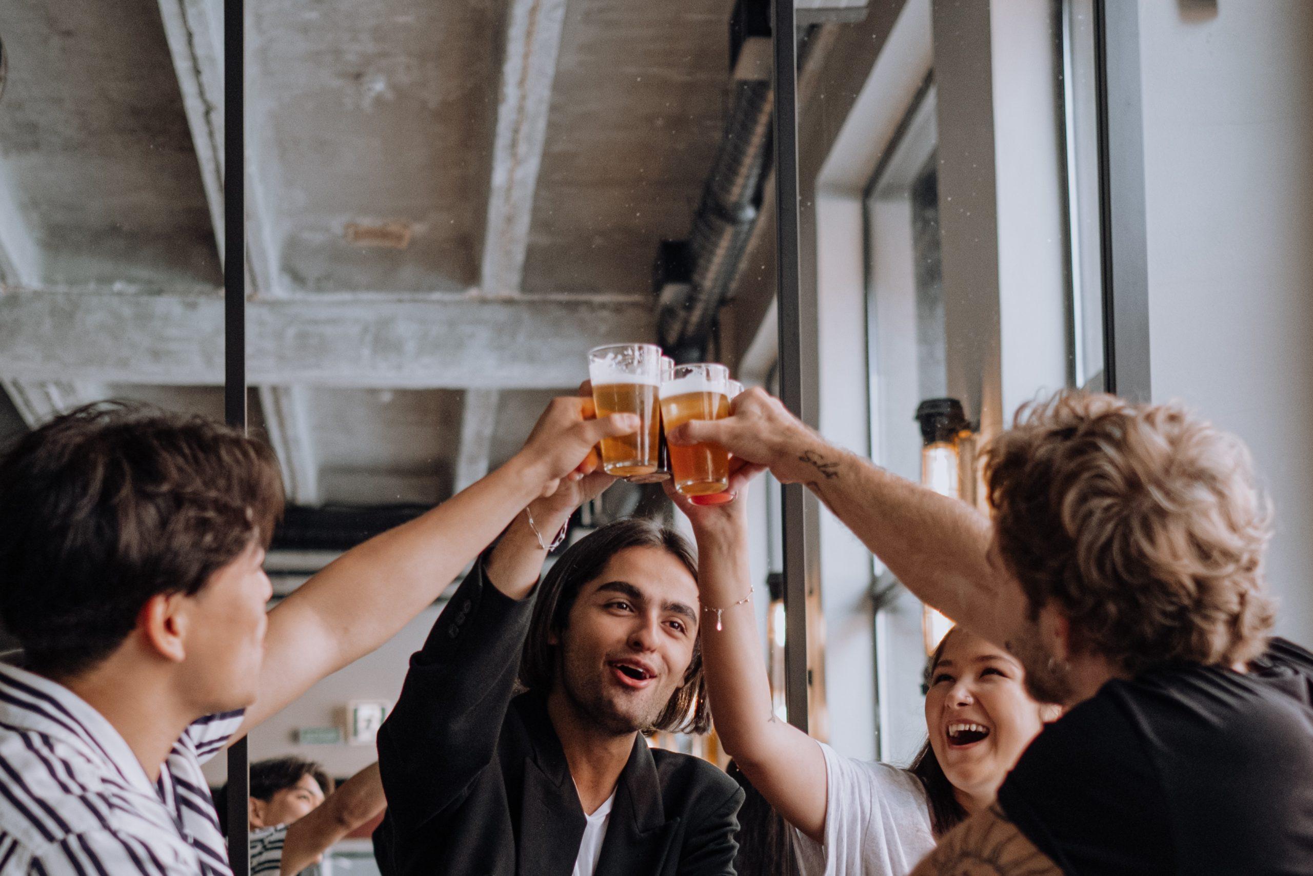 Mensche stossen mit Bier an