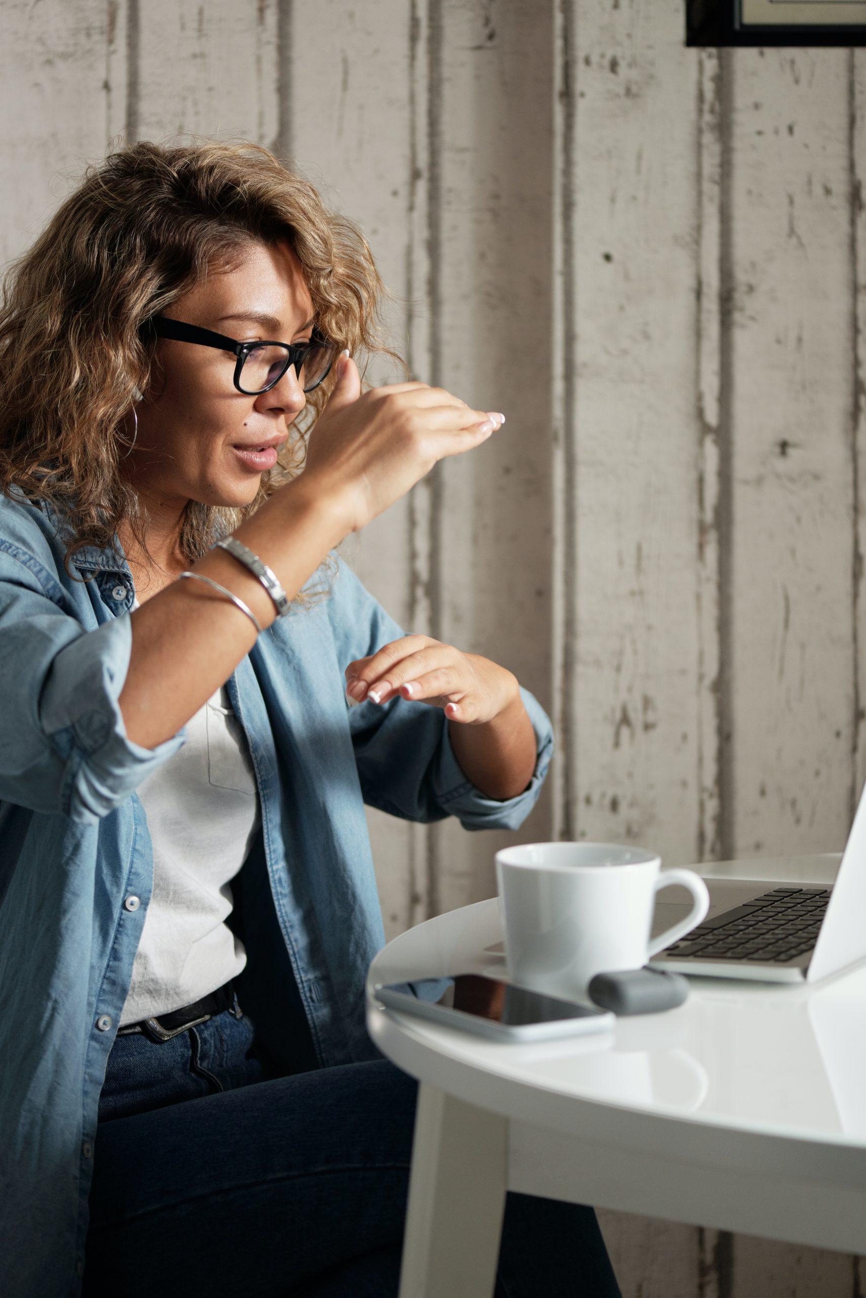 Frau gestikuliert und hält ein Online Meeting am Laptop